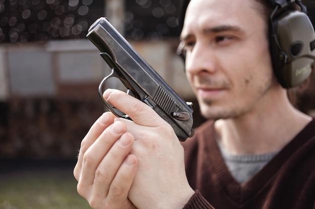 젊은 남자가 목표물을 겨냥하여 총을 쏜다. 보호용 헤드폰을 착용하는 남자. 프리미엄 사진