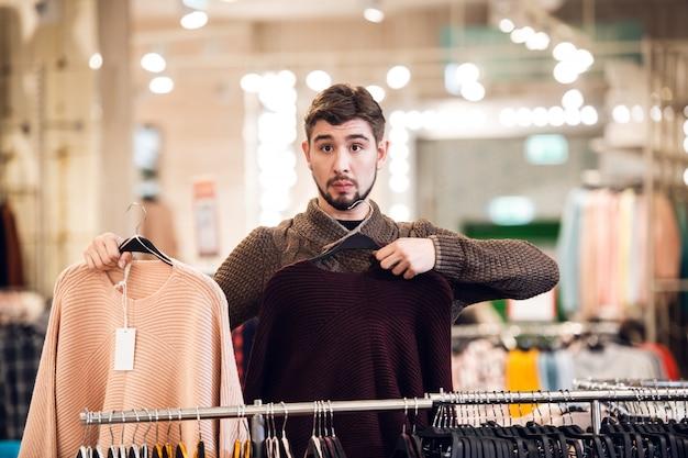 Молодой человек показывает своей девушке доступные цвета свитеров в женском универмаге