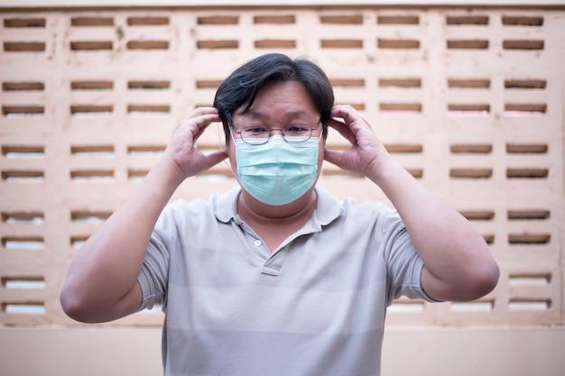 Молодой человек болен, надев маску на лицо для защиты от инфекций и вирусов (covid-19)