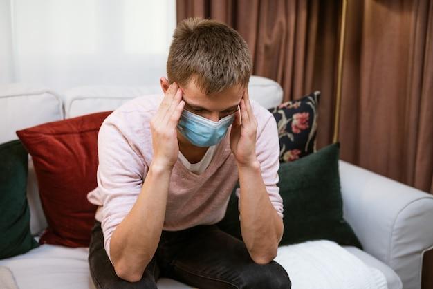 Молодой человек сидит дома на диване, руками держит голову в защитной маске, головные боли при болезни как симптомы
