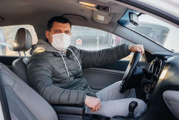 젊은 남자는 유행성 및 코로나 바이러스 동안 운전하는 동안 개인 안전을 위해 마스크를 쓰고 바퀴 뒤에 앉아 있습니다. 감염병 유행.