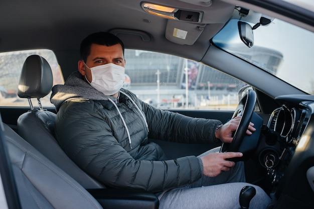 한 청년이 대유행 및 코로나 바이러스 동안 운전하는 동안 개인 안전을 위해 마스크를 쓰고 바퀴 뒤에 앉아 있습니다. 감염병 유행.