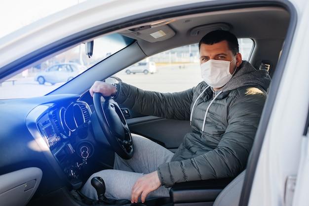 젊은 사람이 개인 안전 마스크를 쓰고 바퀴 뒤에 앉아