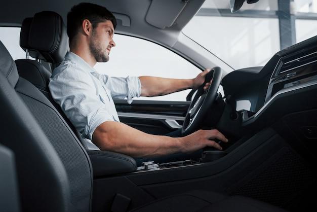젊은 남자는 방향 키에 손을 잡고 새로 구입 한 자동차에 앉아있다.