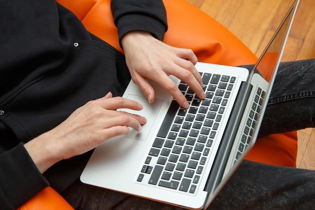 한 젊은 남자가 안락 의자에 앉아 컴퓨터에서 일합니다.
