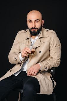 Молодой человек сидит на черной стене и пьет алкогольный напиток.