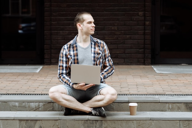 Молодой человек сидит напротив здания с ноутбуком и смотрит вдаль на город