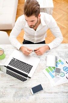 Молодой человек сидит за столом с портативным компьютером.