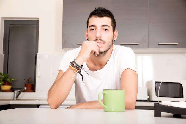 台所に座ってコーヒーを飲む若い男。