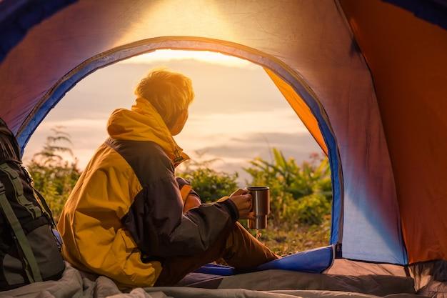 コーヒーカップを持ってテントの中で座っている若い男