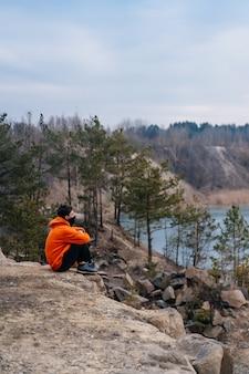 崖の端に座っている若い男