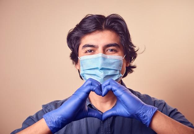 若い男がサージカルマスクを顔につけた手袋をはめて微笑む。