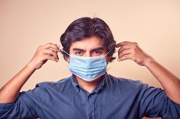 若い男は彼の顔にサージカルマスクとニトリル手袋を着用しながら微笑む