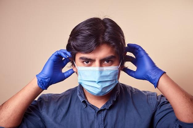 Молодой человек улыбается в нитриловых перчатках с хирургической маской на лице