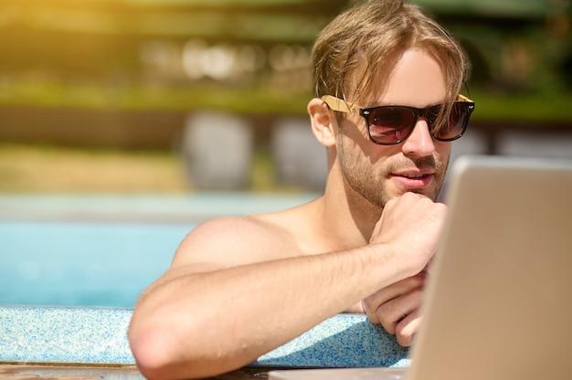 Молодой человек проводит время в бассейне и что-то ищет в интернете
