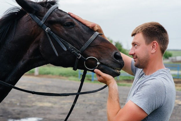 Молодой человек стоит и смотрит на породистого жеребца на ранчо. животноводство и разведение породистых лошадей.