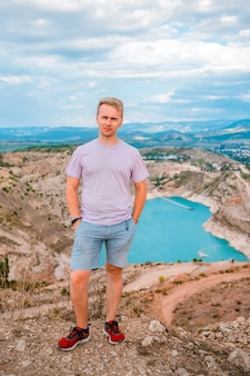 クリミア半島のターコイズブルーの水でハートの形をした採石場に若い男が立っています