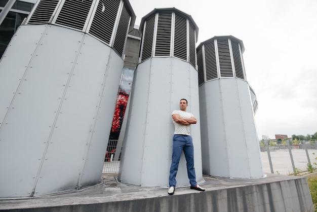 Молодой человек стоит на открытом воздухе возле технических сооружений