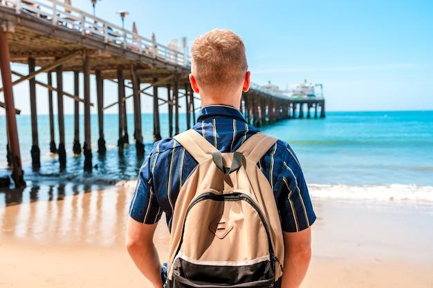 Молодой человек стоит возле пирса на пляже малибу в калифорнии.