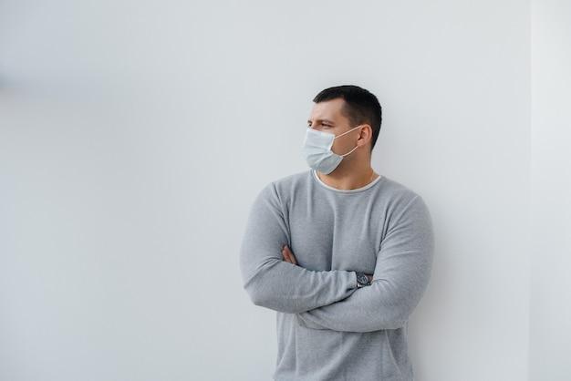 空きスペースのある検疫中に、若い男がマスクをかぶった灰色の壁に立っています。マスク内の検疫。