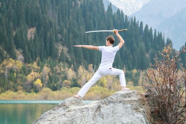 한 청년이 큰 돌 위에 서서 손에 일본도를 들고 있습니다.