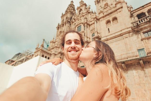 若い女性が自分撮りをして彼のガールフレンドが彼にキスしている間笑顔