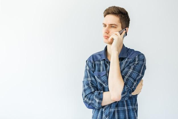 Молодой человек разговаривает по телефону на светло-сером фоне. человек думал