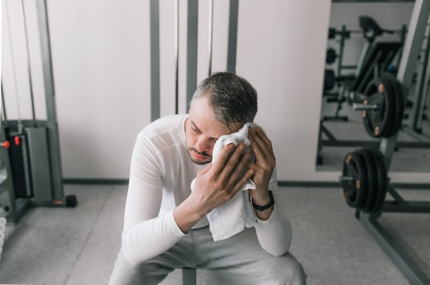 Молодой человек, уставший после тяжелой тренировки, сидит и вытирает пот с лица полотенцем в спортивном клубе. отдых восстановление.