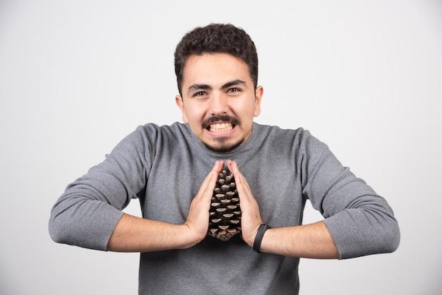 Молодой человек пытается сломать большую сосновую шишку.