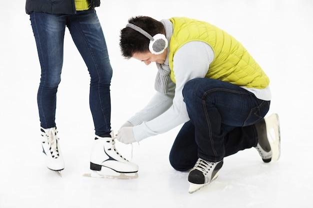 スケートリンクで彼の友人のスケートを結ぶ若い男