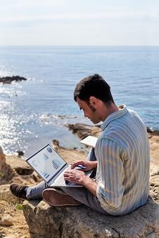 Молодой человек использует свой ноутбук и блокнот во время удаленной работы на побережье