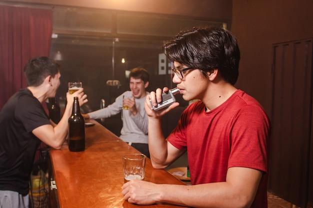 酔っ払った友達がバーで笑ってビールを飲みながら、若い男がたばこを吸う。