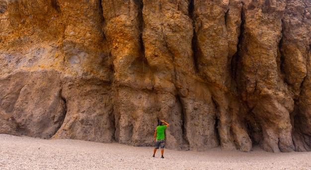 Молодой человек осматривает красивые природные стены плайя-де-лос-муэртос в природном парке кабо-де-гата, нихар, андалусия. испания