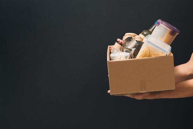 Молодой человек-волонтер держит ящик для пожертвований с продуктами.