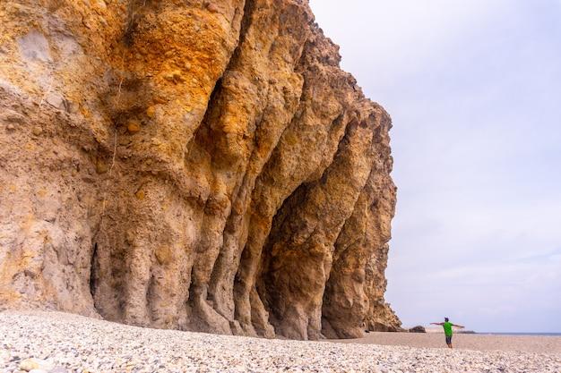 Молодой человек гуляет и смотрит на красивые природные стены плайя-де-лос-муэртос в природном парке кабо-де-гата, нихар, андалусия. испания