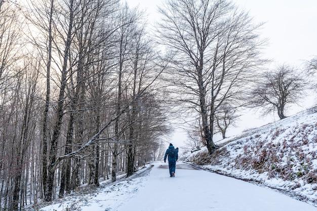 ギプスコアのアイスコリ山に登る道を歩いている若い男。冬の雪による雪景色。