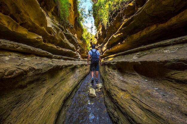 Молодой человек идет по каньону национального парка найваша адские ворота, полному животных. прогулка по кении или сафари на велосипеде