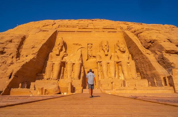 ナセル湖の隣にあるヌビアのエジプト南部のアブシンベル神殿に向かって歩いている若い男。ファラオラムセス2世の寺院、旅行のライフスタイル