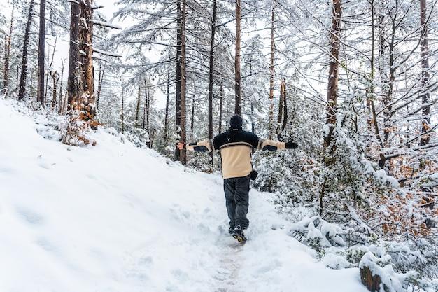 Молодой человек в белом шерстяном свитере гуляет по заснеженному лесу природного парка артикуца в ойарцуне