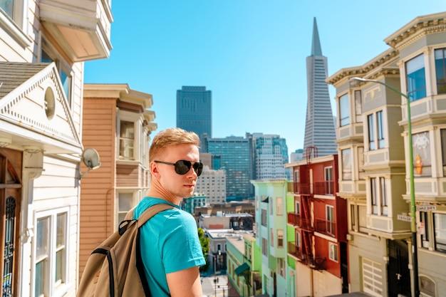 한 젊은이가 샌프란시스코의 transamerica tower가 보이는 아름다운 거리를 걷고 있습니다.