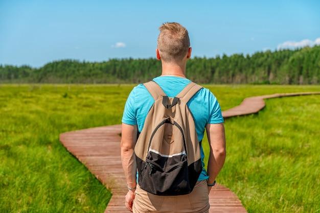 Молодой человек идет по живописной деревянной пешеходной дорожке через болото с высокой травой.