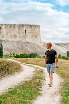 クリミア半島を旅するための旗である白い岩の近くの田舎道を若い男が歩く