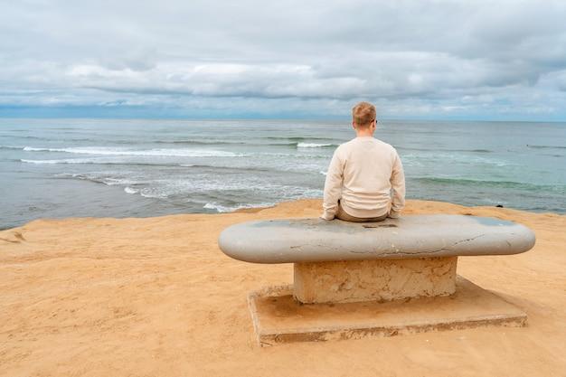 Молодой человек гуляет по тихому океану в природном парке sunset cliffs в сан-диего