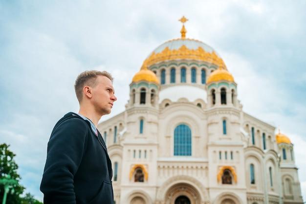 러시아 크론슈타트의 바다 대성당이 있는 광장을 걷고 있는 청년