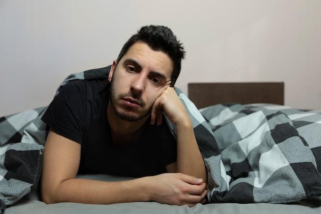 ソファーで寝ながらテレビを見ている若い男。