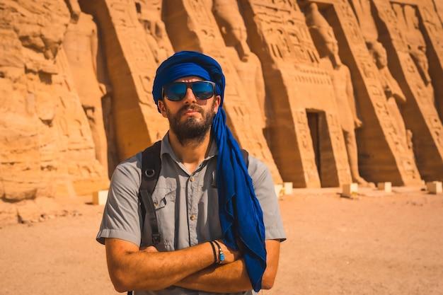ナセル湖の隣にあるヌビアのエジプト南部のアブシンベル近くにあるエジプトのネフェルタリ神殿を訪れる青いターバンを着た若い男。ファラオラムセス2世の寺院、旅行のライフスタイル