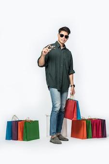 어두운 셔츠와 청바지를 입은 청년이 신용 카드로 쇼핑하러 여러 가방을 들고