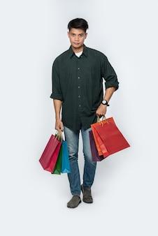 濃い色のシャツとジーンズを着た若い男が買い物に行くためにたくさんのバッグを持っています