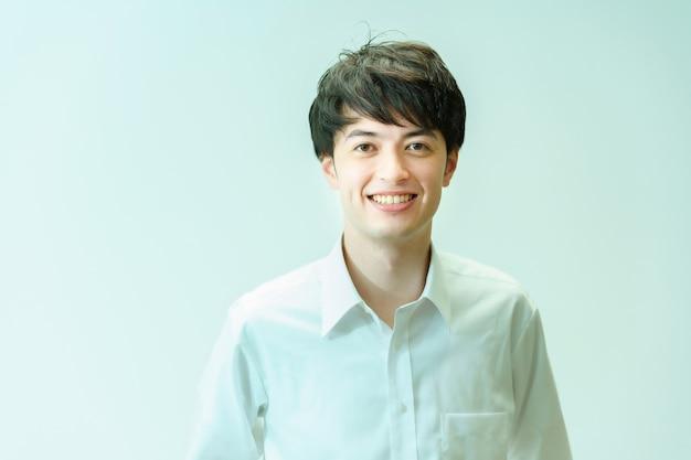 Молодой человек в белой рубашке и улыбается на белом фоне