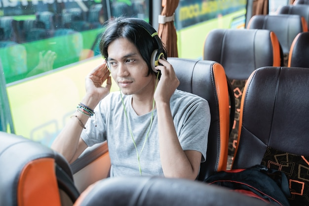 버스 여행에서 창가에 앉아있는 동안 휴대폰에서 음악을 듣는 동안 헤드폰을 착용 한 젊은 남자